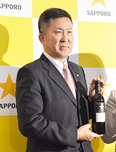 「グランポレール」を手に持つ高島英也社長(22日、ワイン事業方針説明会)