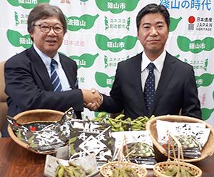 握手する高村一成ケンミン食品社長(左)と小田垣昇小田垣商店常務