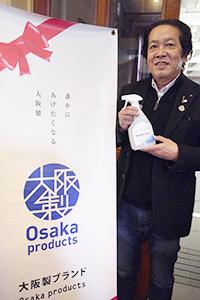 「大阪製」ブランドマークの前で、同品をアピールする川上大雄代表取締役社長CEO