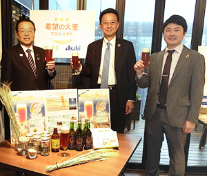 「希望の大麦」で醸造したビールを持つ(左から)渥美巖東松島市長、加賀美昇アサヒグループホールディングス取締役と三井茂史氏(2月28日の試飲会で)