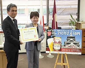 兼松康熊本支社長(左)が宮尾千加子熊本県教育長に目録を贈呈した