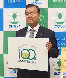 100周年記念ロゴマークを抱えPRする内田和幸会長