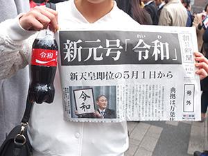 令和デザインのコカ・コーラと号外を手にする人(東京・新橋駅前で)